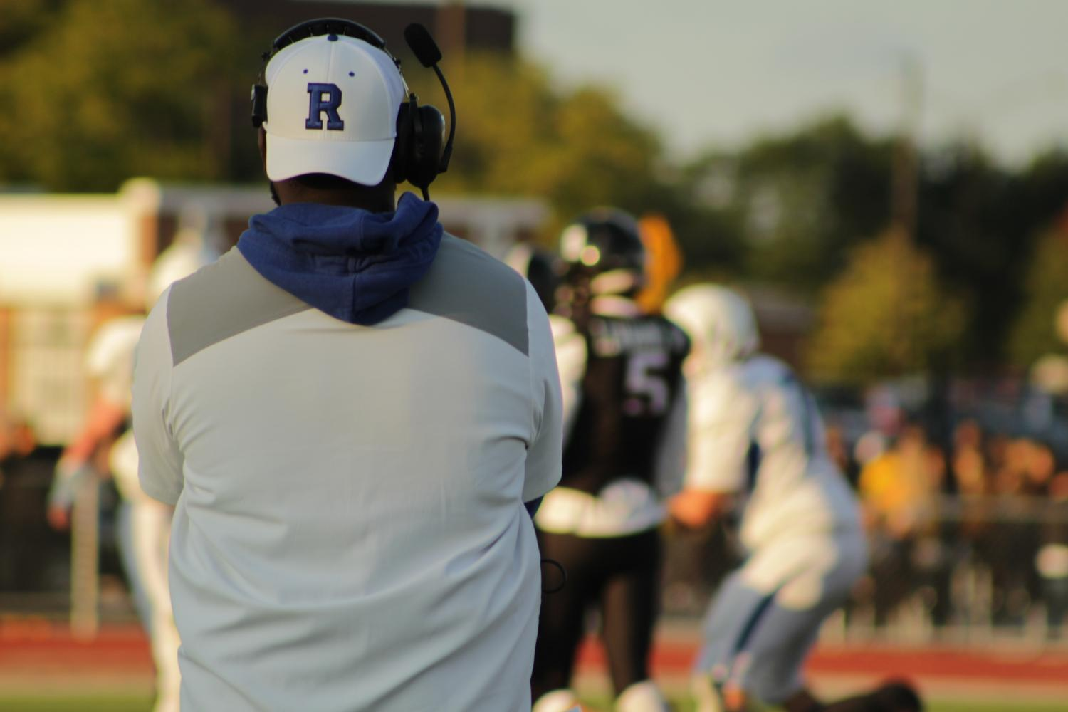 Coach of the Rochester Falcons watches team prepare before the game.