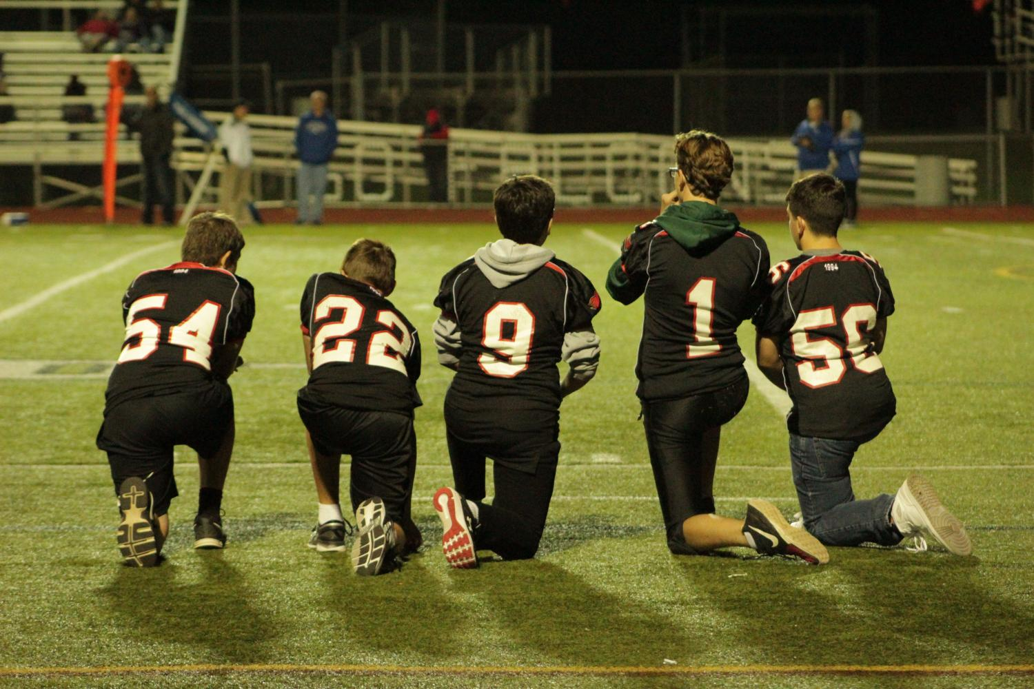 Players on the Junior Varsity team take a knee.