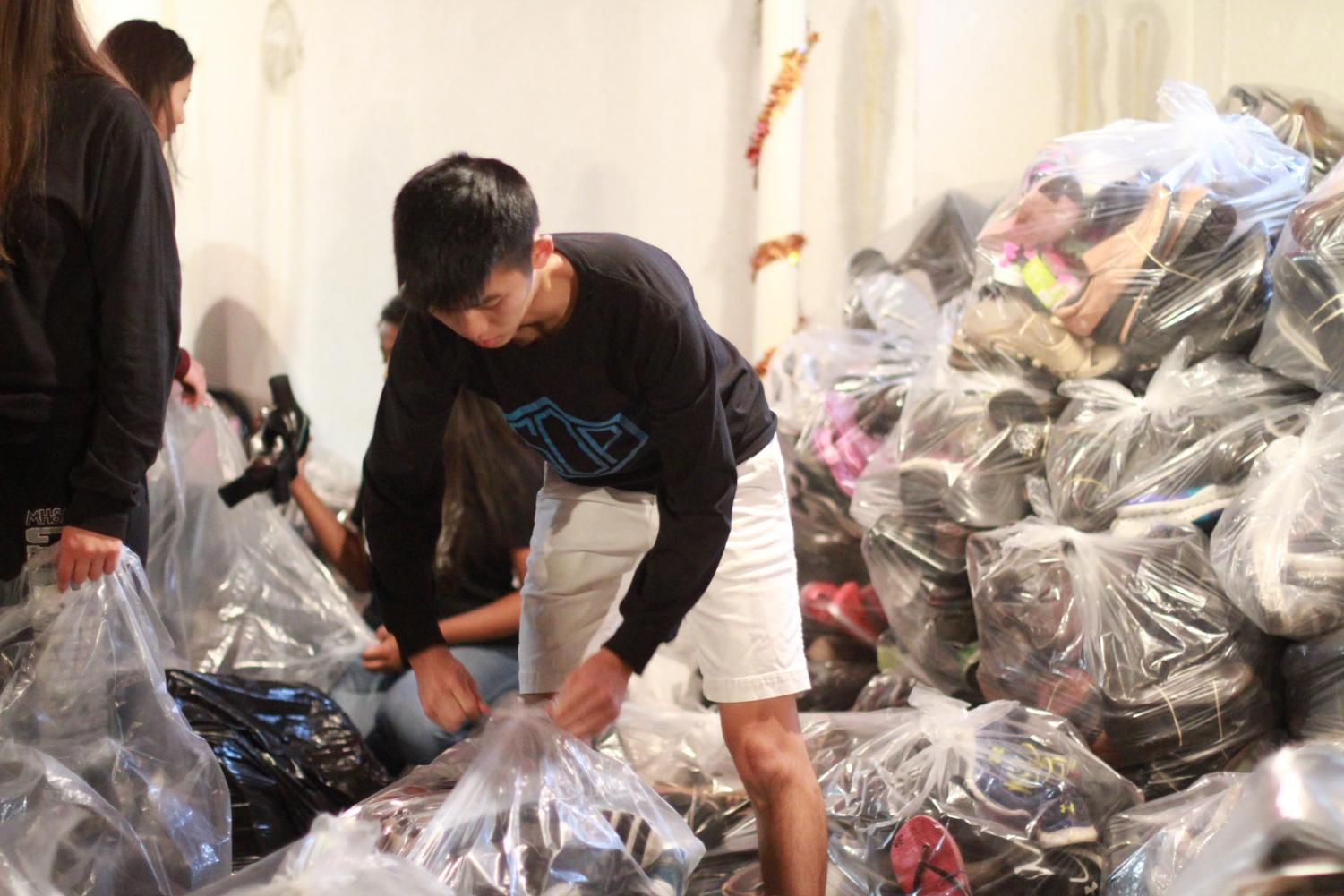 Senior Michael Lin packs shoes at a packing meeting.