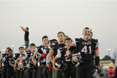 The varsity football team stands for the national anthem at the homecoming game.