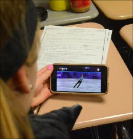 Sophomore Shannon Murphy watches American Adam Rippon in the freestyle portion on her phone.