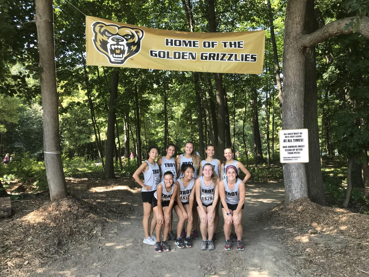 The girls varsity squad pose under the Oakland University cross country banner.
