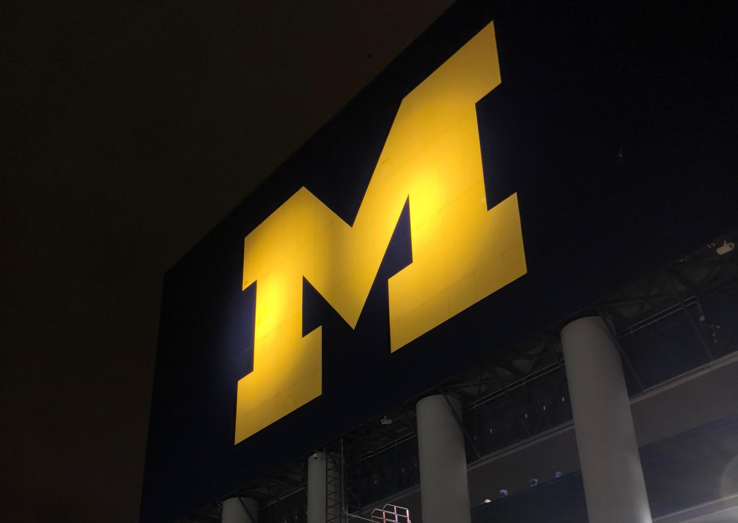 The back of a scoreboard at The Big House at the University of Michigan shines for pedestrians on Main Street in Ann Arbor.