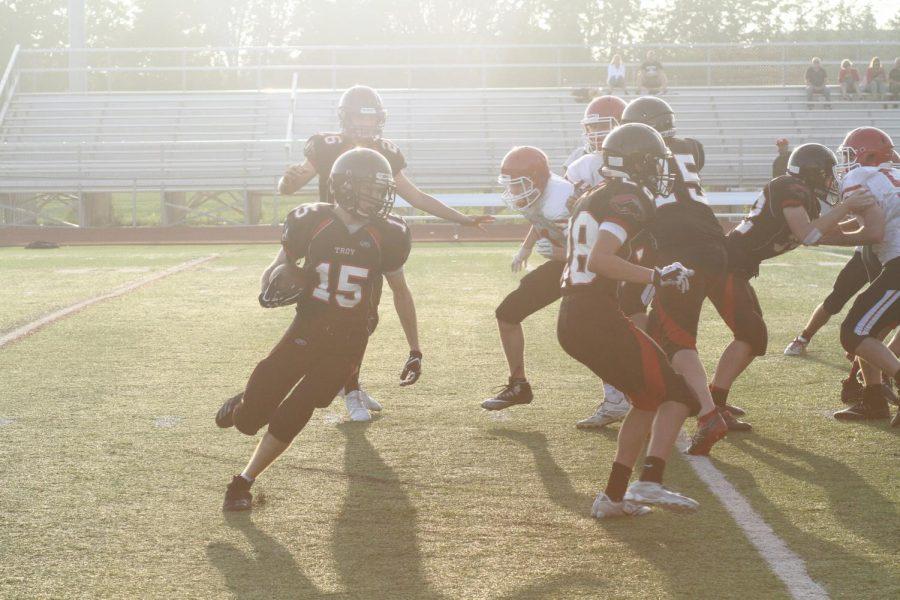 The+Troy+JV+football+team+runs+the+ball+against+Orchard+Lake+St.+Mary%27s.