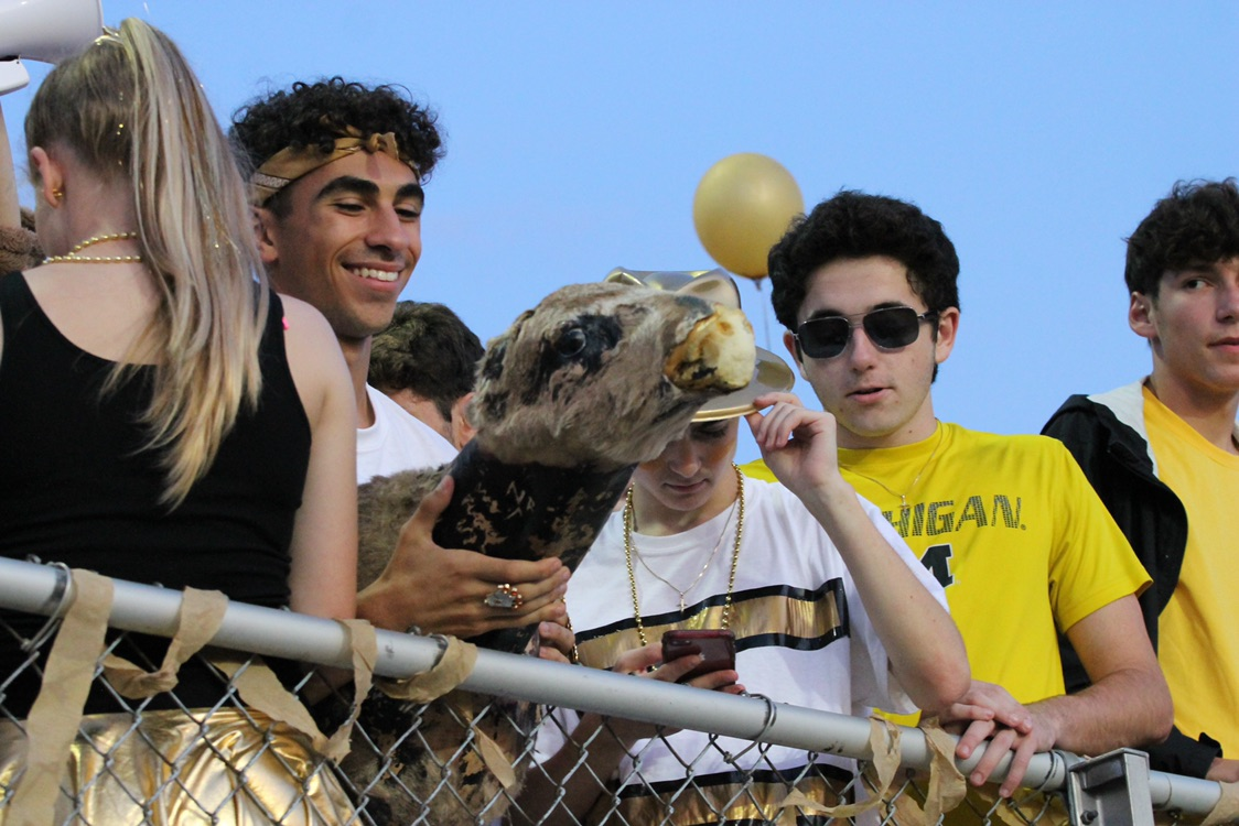 Senior Omar Ibrahim holds the deer head at the gold-out game.