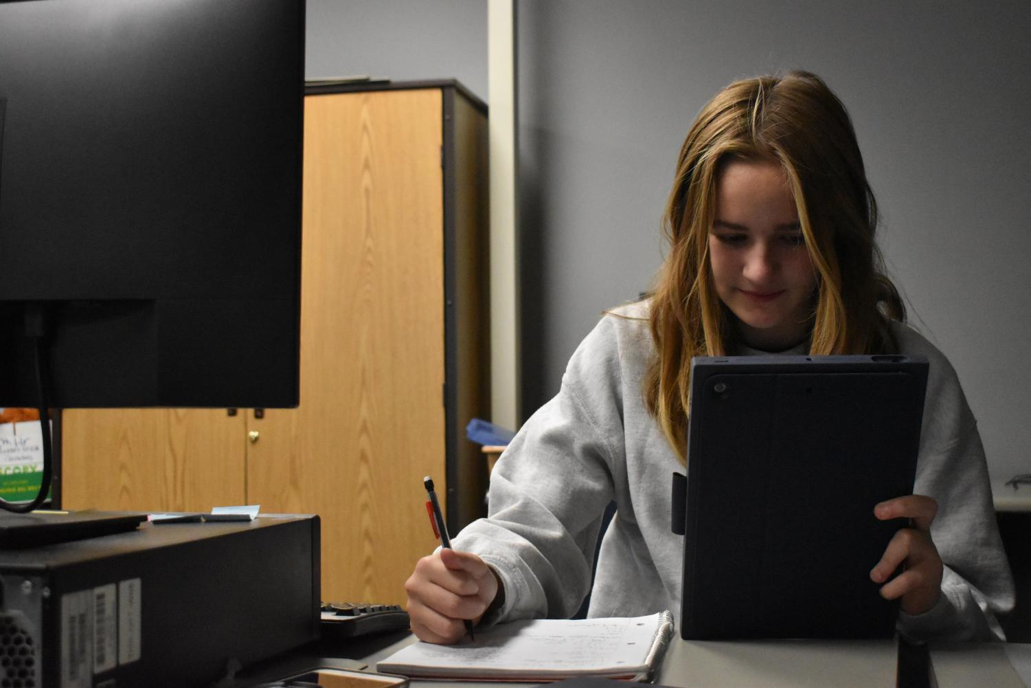 Freshman Ella Koweck works on her iPad given to her by the school.